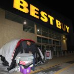 Stefan Rood, 20, cleans out his tent outside a Best Buy in Mayfield Heights, Ohio while waiting for the store to open at 12 a.m. on Friday. Rood, who has been camped out since Wednesday night, is looking to buy a new cell phone. (AP Photo/Tony Dejak)
