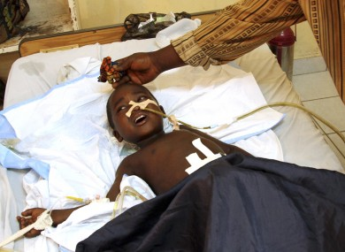 An 11-year-old boy, accompanied by his father, receives treatment at the HEAL Africa hospital after being shot in the abdomen during a firefight between Congolese police and attacking M23 rebels.