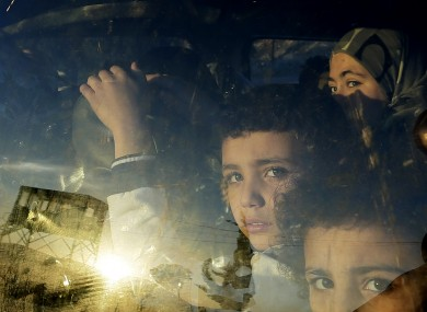 Syrian children look through their car window as they cross into Lebanon with their families at the border crossing, in Masnaa, eastern Lebanon