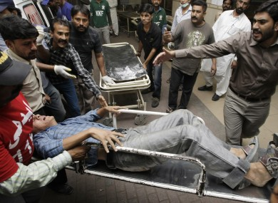 People rush an injured man to an emergency ward of a local hospital in Karachi, Pakistan after the attacks