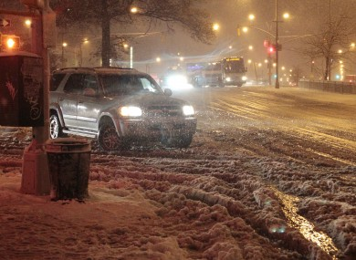 Cars navigate Queens Boulevard, New York, during a snow storm yesterday.