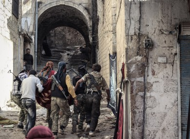 Free Syrian Army fighters carry a wounded colleague through the town of Harem in Syria