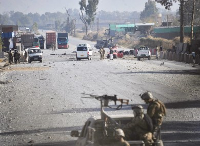 Afghan security forces block the road where Taliban suicide bombers attacked a joint U.S.- Afghan air base in Jalalabad.