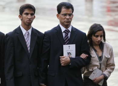 Husband of late Jacintha Saldanha, Benedict Barboza, center, son Junal, 16, and daughter Lisha, 14, arrive at Westminster Cathedral in London for a memorial service.