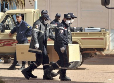 Algerian firemen carry a coffin containing a person killed during the hostage situation earlier today