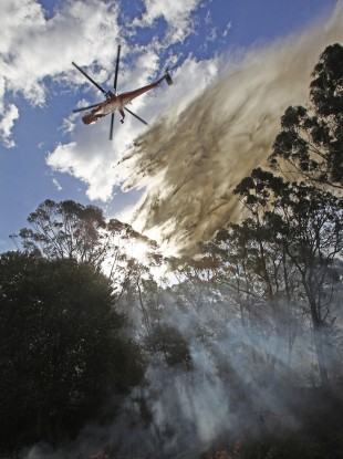 A helicopter drops water onto a smoldering fire in the Lane Cove National Park in Sydney