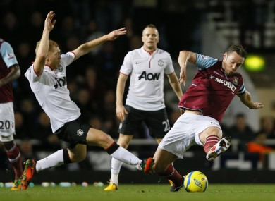 Paul Scholes and Kevin Nolan compete for the ball.