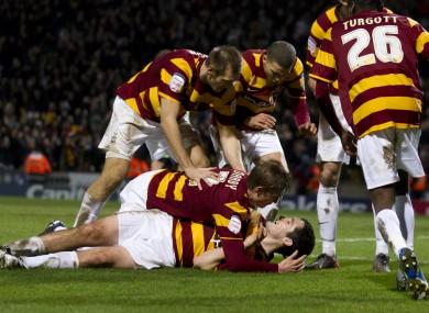 Bradford City's Carl McHugh, bottom, celebrates with jubilant teammates.