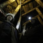 Coal miners Semsa Hadzo, left, and Sakiba Colic, right, Bosnian coal technologists, walk through the underground tunnels of the coal mine.