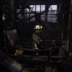 A Bosnian miner rides an elevator on the way down the coal shaft of the mine in Breza.