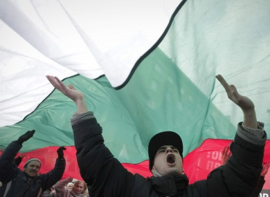 Bulgarian shouts slogans as they carry giant Bulgarian flag during a protest in Sofia.