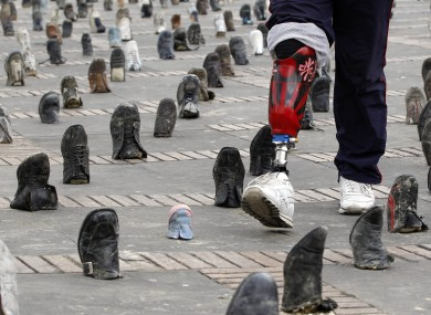 A Colombian amputee soldier, victim of a landmine, walks through a shoe installation marking International Day for Landmine Awareness in Bogota on 4 April, 2011.