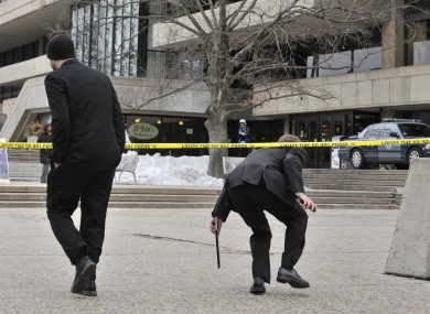 Pedestrians on the MIT Campus in Cambridge, Mass., duck underneath police tape