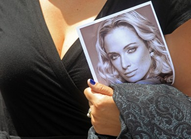 A woman holds a photo of Reeva Steenkamp, as she leaves her funeral, in Port Elizabeth earlier.