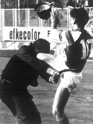Dinamo Zagreb's captain, Zvonimir Boban, attacks a police officer during soccer fan riots, prior to their match against Red Star Belgrade, Zagreb, Croatia, May. 13, 1990.