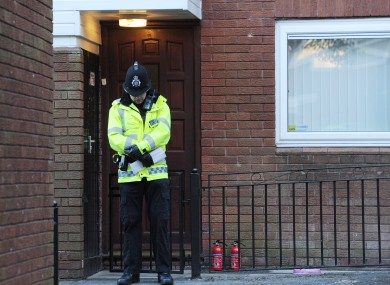 A Police officer stands outside the front door of the house in Chaucer Grove, Atherton