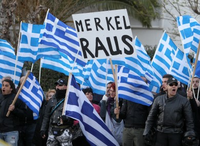 Supporters of the far-right party Golden Dawn with Greek flags hold signs reading 'Merkel out' in German, during a protest outside the Germany embassy in Athens on Friday.