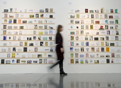 An exhibition assistant walks past art work at the RCA Secret 2013 exhibition at the college's Dyson House, south London building.