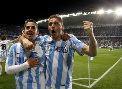 Malaga's Isco Alarcon from Spain, left, celebrates with teammate Joaquin Sanchez after scoring against FC Porto during the Champions League round of 16 second leg match.