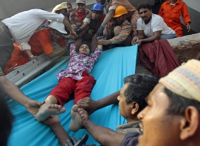Rescuers lower down a survivor from the debris of a building that collapsed in Savar, near Dhaka.