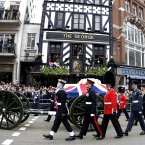 A flag draped coffin bearing the body of former Prime Minister Margaret Thatcher is carried on a gun carriage drawn by the King's Troop Royal Artillery during her ceremonial funeral procession. (Matt Dunham/PA Wire)