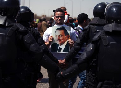 A supporter holds a photo of Egypt's ousted president Hosni Mubarak as riot police stand guard outside a courtroom in Cairo, Egypt, earlier this week.