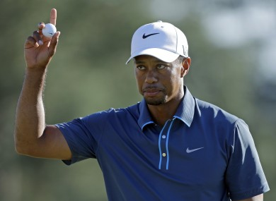 Tiger Woods holds up his ball after putting out on the 18th hole during the third round of the Masters golf tournament.
