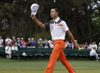 Amateur Guan Tianlang, of China, waves his cap after putting out on the 18th hole during the fourth round of the Masters golf tournament.