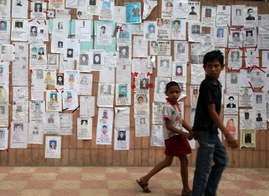 Two boys walk past a wall showing flyers of missing people near the collapsed factory in Bangladesh