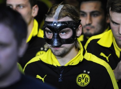 Dortmund's Marcel Schmelzer wears a protective mask as he enters the pitch.