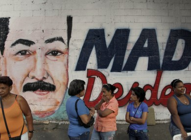 Residents wait to enter a polling station where a nearby wall is covered with a mural of interim President Nicolas Maduro during the presidential election in Caracas, Venezuela, today.