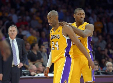 Los Angeles Lakers guard Kobe Bryant, center, is consoled by forward Metta World Peace, right, as head coach Mike D'Antoni looks on after being injured during the second half of their NBA basketball game against the Golden State Warriors.