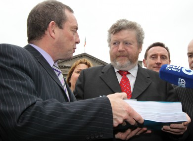 Health minister James Reilly receives the report of the Oireachtas Health committee on the proposed abortion laws, from its chairman Jerry Buttimer. Buttimer's committee will be called into action again to discuss the draft proposals.
