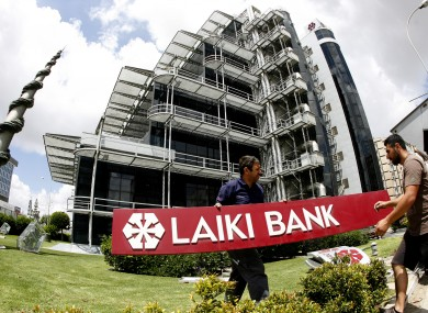 Workers take down the signs at the headquarters of Cyprus' now defunct bank Laiki in Nicosia today.