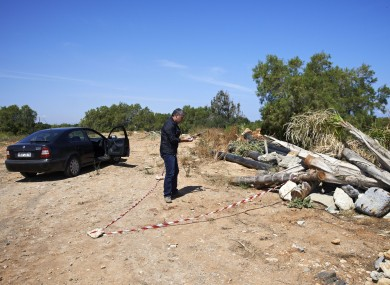 A plain clothed police officer investigates an area where a 12-year-old Russian boy was found wounded in the holiday resort of Hersonissos, on the Greek island of Crete.