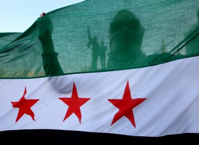 A Syrian activist is silhouetted through the Syrian revolution flag.