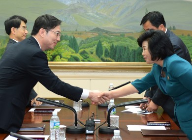 South Korea's Unification Policy Officer Chun Hae-sung, left, shakes hands with the head of North Korea's delegation Kim Song Hye.