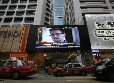 A TV screen shows a news report of Edward Snowden in Hong Kong yesterday