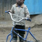 A young boy holds a broken bicycle in the Kibera slum in Nairobi, when the leaders of the world's wealthiest nations meet during the G8 summit to discuss helping the poorest people on the planet in 2005. (AP Photo/Karel Prinsloo)