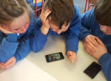 Sixth class children helping junior infants develop early reading skills on iPods.