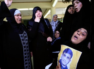 The mother of Hezbollah fighter Saleh Sabagh, 18, who was killed in a battle against Syrian rebels in the Syrian town of Qusair, right, mourns and holds his picture during his funeral, in the southern port city of Sidon, Lebanon