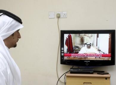 A man watches a televised address by Qatar's Emir Sheik Hamad bin Khalifa Al Thani, in Doha today