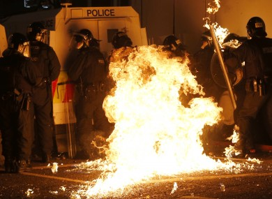 A petrol bomb hits riot police after it was thrown by loyalist rioters in the Woodvale area of north Belfast.