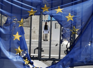 File photo of a Greek presidential guard stands framed bythe remains of a European Union flag half-burnt by protesters in Athens