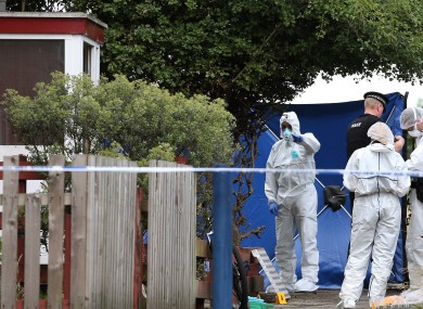 Police forensic officers working at the scene of a stabbing in Moston, Manchester.