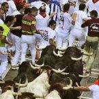 Revelers run beside raging bulls in Spain. (AP Photo/Alvaro Barrientos)