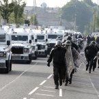 PSNI in riot gear move into position to escort Orange feeder parade past the Ardoyne shops, in Belfast (Paul Faith/PA)