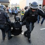 An injured Police Service of Northern Ireland (PSNI) officer is helped by colleagues (Image: Paul Faith/PA)