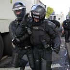 An injured PSNI Police officer in full riot gear as they stop the filter parade (Julien Behal/PA Wire)