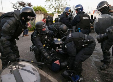 An injured PSNI officer helped by colleagues during July 12th riots.